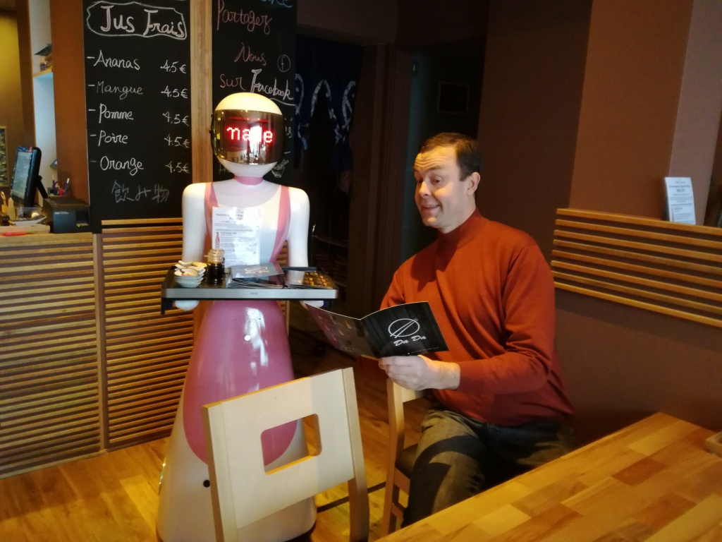 Female robot serving Transmedia.online founder reading menu in restaurant.